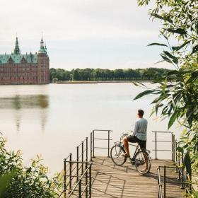 Cyclist stands looking at Frederiksborg Castle across the moat